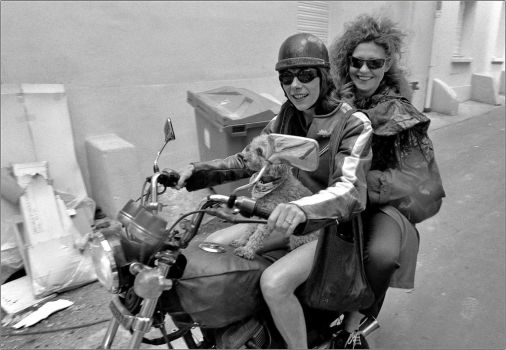 Two women and a dog on a bike by SUDOR