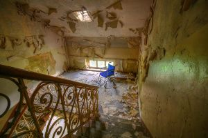 Wheelchair in abandoned hospital by mjagiellicz