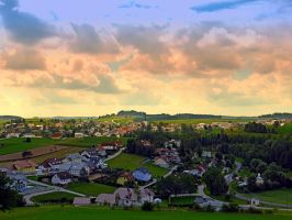 Beautiful village skyline beyond cloudy sky by patrickjobst