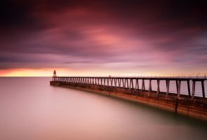 Whitby Pier at sunset by kharashov