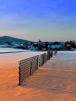 Fences, evening sun and the village by patrickjobst